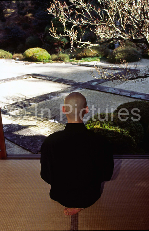 """A Zen monk meditates before a rock garden..Sitting Zen (or Zazen) is at the heart of Buddhist practice in Japan..In Zen Buddhism, zazen (literally """"seated meditation"""") is a meditative discipline practitioners perform to calm the body and the mind and experience insight into the nature of existence and thereby gain enlightenment (satori)"""