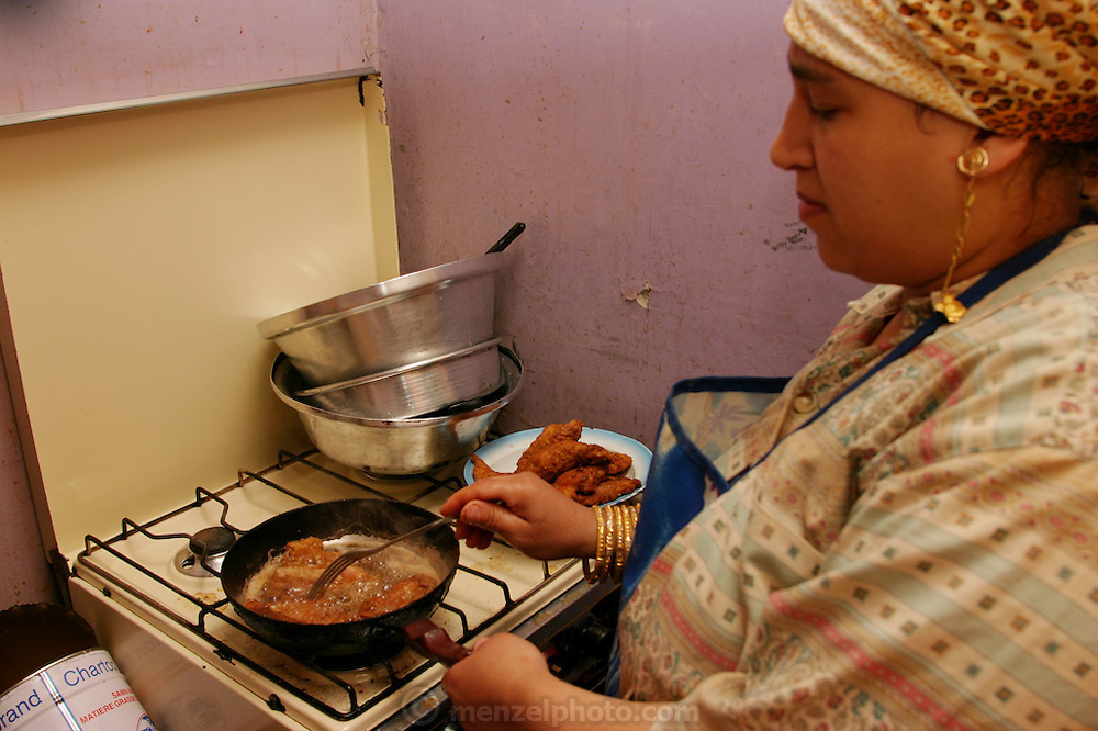 (MODEL RELEASED IMAGE). Nadia Ahmed fries chicken in the tiny kitchen of her fourth-floor apartment in the old section of Islamic Cairo, Egypt. (Supporting image from the project Hungry Planet: What the World Eats.)