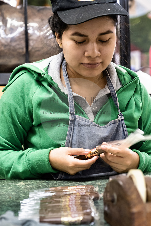 A female worker wraps the cigar band on finished fine cigars before packaging at the Santa Clara cigar factory in San Andres Tuxtlas, Veracruz, Mexico. The factory follows traditional hand rolling using the same process since 1967 and is considered by aficionados as some of the finest cigars in the world.