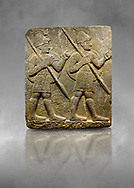 Hittite monumental relief sculpted orthostat stone panel from the Herald's Wall. Basalt, Karkamıs, (Kargamıs), Carchemish (Karkemish), 900-700 B.C. Military parade with soldiers. Anatolian Civilisations Museum, Ankara, Turkey<br /> <br /> Two helmeted soldiers marching soldiers in short skirts carry the shield on their backs and the spears in their hands.  <br /> <br /> Against a grey art background. .<br />  <br /> If you prefer to buy from our ALAMY STOCK LIBRARY page at https://www.alamy.com/portfolio/paul-williams-funkystock/hittite-art-antiquities.html  - Type  Karkamıs in LOWER SEARCH WITHIN GALLERY box. Refine search by adding background colour, place, museum etc.<br /> <br /> Visit our HITTITE PHOTO COLLECTIONS for more photos to download or buy as wall art prints https://funkystock.photoshelter.com/gallery-collection/The-Hittites-Art-Artefacts-Antiquities-Historic-Sites-Pictures-Images-of/C0000NUBSMhSc3Oo