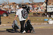A parent at tornado-damaged Briarwood elementary school carries her children's backpacks after firefighters retreived them in Oklahoma City, Oklahoma May 22, 2013.  No students were killed at this school. Rescue workers with sniffer dogs picked through the ruins on Wednesday to ensure no survivors remained buried after a deadly tornado left thousands homeless and trying to salvage what was left of their belongings.  REUTERS/Rick Wilking (UNITED STATES)