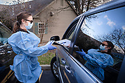 """15 NOVEMBER 2020 - WEST DES MOINES, IOWA: Dr. ANNA HOLZER checks in a patient for a drive up rapid COVID test in West Des Moines. Hundreds of people lined up for drive up COVID-19 tests at the Doctors NOW clinic in West Des Moines. Iowa is seeing a surge in COVID-19 (Coronavirus) cases and the state's """"Test Iowa"""" public testing program is swamped with some people waiting 3 - 5 days for an appointment for a drive up test. As of Sunday, 15 November, Iowa had the 3rd highest Coronavirus (SARS-CoV-2) infection rate in the country with 4,432 new cases reported in the previous 24 hours and 1,279 people hospitalized for COVID-19. Des Moines area hospitals have warned that they are at capacity and many hospitals are reporting staffing shortages because workers have come down with COVID-19.     PHOTO BY JACK KURTZ"""