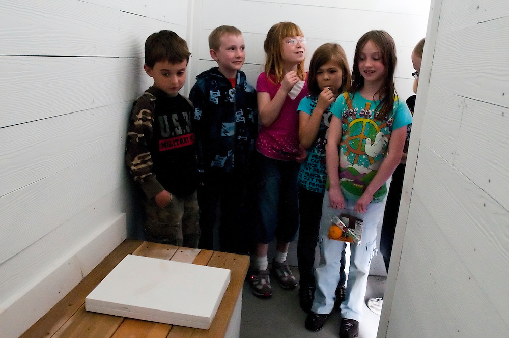 Matt Dixon | The Flint Journal..Students from Ami Unger's second grade class at Siple Elementary in Davison take a brief tour of a mock outhouse while visiting the Kitchen School in Davison Wednesday afternoon. Named after Silas Kitchen, an early homesteader of Davison, The Kitchen School is hosting a program for Davison elementary school students, providing a one-room school-house learning experience. The school was founded in 1847 and moved to this building, which has been restored to a 1940s state, sometime between 1867 and 1870.