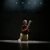 """A Palestinian Circus School member holds a branch of an olive tree as a symbole to peace, during the show """"Circus behind the wall"""" in Ramallah, November 20, 2009. The circus group was established in 2006, in order to give a new way of expression for Palestinians, and a new way to deliver the idea of resistance to the occupation. This performance shows the life of Palestinians behind the separation wall. Photo by Michal Fattal/Backyard"""