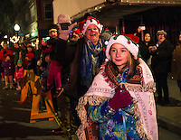 Emma Fabian watches as Santa and Mrs. Claus come down Main Street during the annual Holiday Parade on Sunday evening.  (Karen Bobotas/for the Laconia Daily Sun)