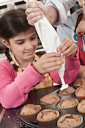 Close-up of girl icing on muffins with icing bag in home economics class, Bavaria, Germany