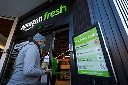 "© Licensed to London News Pictures. 07/03/2021. LONDON, UK.  A customer enters the new 2,500 sq ft Amazon Fresh store in Ealing, west London on its first weekend of opening. It is the first ""just walk out"" grocery store in the UK and the first outside the USA.  As a ""contactless"" shop, it is available to anyone signed up to Amazon and with the app on their smartphone.  In-store cameras and artificial intelligence monitor customers picking up items who simply walk out and billing takes place later automatically.  Photo credit: Stephen Chung/LNP"
