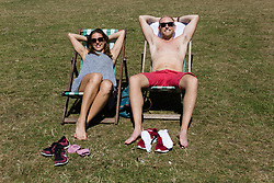 © Licensed to London News Pictures. 12/08/2016. LONDON, UK.  Tourists, Elena from Italy and Drew from Australia enjoy the first day of their holiday in London as they sunbathe during the hot and sunny weather today in Green Park in London this lunchtime.  Photo credit: Vickie Flores/LNP