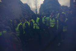 19 January 2019. Paris, France.<br /> Gilets Jaunes - Acte X take to the streets of Paris. As seen through a Tricolour.  An estimated 7,000 people took part in the looping 14 km route from Place des Invalides to protest tax hikes from the Government of Emmanuel Macron imposed on the people. An estimated 80,000 people took part in protests across the country. Regrettably the movement has attracted a violent element of agitators who often face off with riot police at the end of the marches which tends to deflect attention away from the message of the vast majority of peaceful protesters.<br /> Photo©; Charlie Varley/varleypix.com