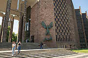 Victory over the Devil, a sculpture by Jacob Epstein outside Coventry Cathedral with St Michaels also known as St Michaels, a modern cathedral founded in 1956 on 23rd June 2021 in Coventry, United Kingdom. The Cathedral Church of Saint Michael, commonly known as Coventry Cathedral, is the seat of the Bishop of Coventry and the Diocese of Coventry within the Church of England. The current St Michaels Cathedral, built next to the remains of the old, was designed by Basil Spence and Arup, built by John Laing and is a Grade I listed building.