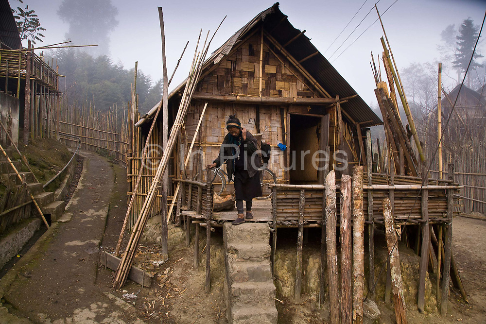 An Apatani tribal woman walks through the rows of bamboo huts on stilts in the village of Hijja, Arunachal Pradesh. The Apatani tribe are one of hundreds of indigenous tribes scattered across India, particularly the north east. Their origins are from Mongolian nomadic tribes whom settled on the Ziro plateau, close to the Chinese border, they practice fixed agriculture as well as forestry, planting trees on the rim of the plateau as well as bamboo forests from which they derive fire wood, building their homes as well as using the bamboo for all manner of applications in their daily lives, cooking utensils and household containers amongst other uses. They carefully cultivate bamboo forests allowing them to grow, but not flower and die, as this would spell disaster for their very own existence. They also tend to their rice fields and live stock for what is mostly a subsistence economy. The Indian constitution recognizes over 500 indigenous tribes, which account for 8.5% of the total population.