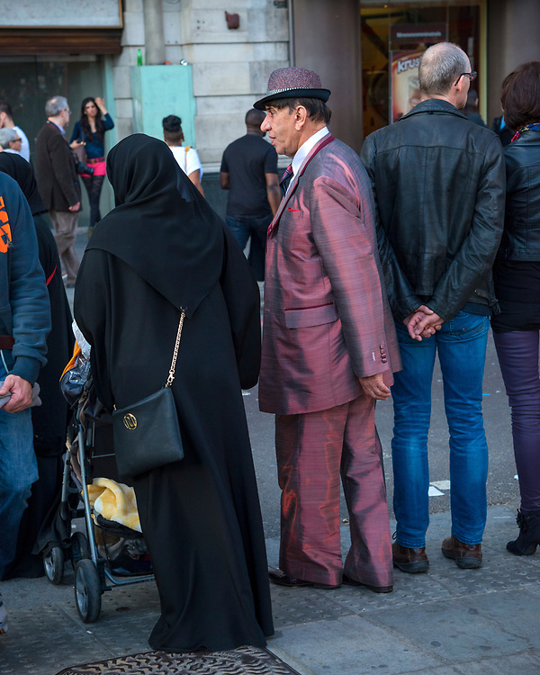 Iridescent Suit on an elderly gentleman in the crowd of People at the top of Oxford Street in London near Marble Arch.  Licensing and Open Edition Prints.
