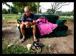 1 July 2006 - New Orleans - Louisiana. Earl Jackson, City Park. 58 yr old Jackson moved to New Orleans from Georgia in October 2005 in search of work. He moved to the unauthorised  migrant workers encampment at City Park, where many workers and drifters lived in tents and trailers. He slept on the outdoor couch the previous night. The camp was forcibly emptied and the residents evicted under court order just after midnight on July 1st. Jackson is the last resident, picking his way through the remnants of the camp. Life has been tough for Jackson, living in a tent in the park next to a creek with snakes, spiders, alligators and mosquitos. His tools were stolen early on, his ride towed. His health has deteriorated. He has a septic spider bite inside his thigh, small flies dine on wounds on his legs, he must shower and shave under an outdoor hose. The only possessions he has left are all kept in a shopping cart. The city removed the mobile toilets forcing Jackson to defecate in the woods. He does not know where he will go now. He will likely end up amongst the city's homeless population.