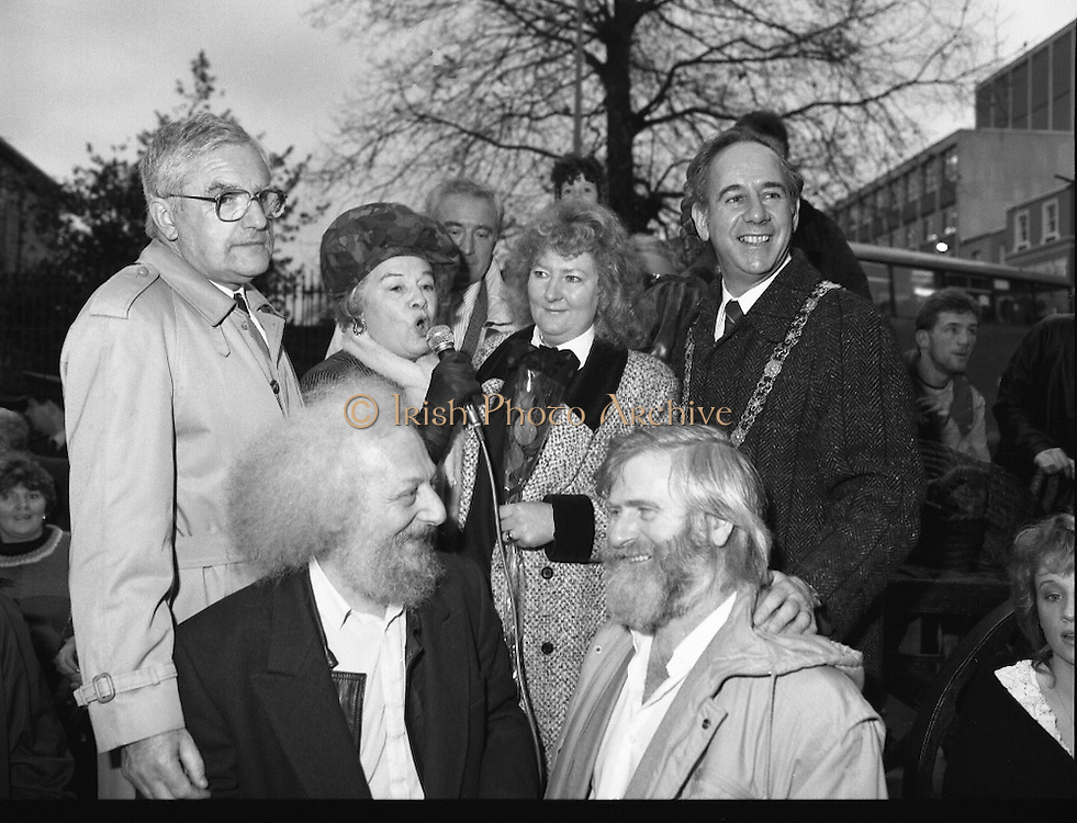"""Molly Malone Statue Unveiled. (R93)..1988..20.12.1988..12.20.1988..20th December 1988..""""Dublin's Fair City"""" received a millenniun gift to commemorate her most famous daughter, Molly Malone, when Jurys Hotel Group plc presented a specially commissioned sculpture to the people of Dublin. The sculpture was formally handed over by Michael McCarthy, MD,Jurys Hotel Group, to the Lord Mayor of Dublin, Councillor Ben Briscoe, TD, in an unveiling ceremony today at the corner of Grafton Street, Suffolk Street and Nassau Street..Molly Malone was created and fashioned in her traditional 17th century dress by Dublin born artist, Jeanne Rynhart, who was selected from a number of entries for the statue design, by the Dublin Millennium Board...Picture shows Alice Glenn TD taking over the mike at the unveiling of the Molly Malone statue..(L-R) Michael Mc Carthy, Eamonn Campbell, Jeanne Rynhart, john Sheehan and Ben Briscoe."""
