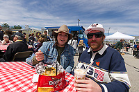 Jaimie Mills and Taylor Stout sit down to a feast of Perogi Poutine, Walking bag of Dorrito Nachos and Street Corn Parfait from the fork ING AWESOME food truck during Tanger Outlet's Exit 20 Food Truck Festival on Saturday.  (Karen Bobotas/for the Laconia Daily Sun)