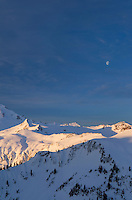 The moon hangs over the North Cascades on a winter morning, Washington