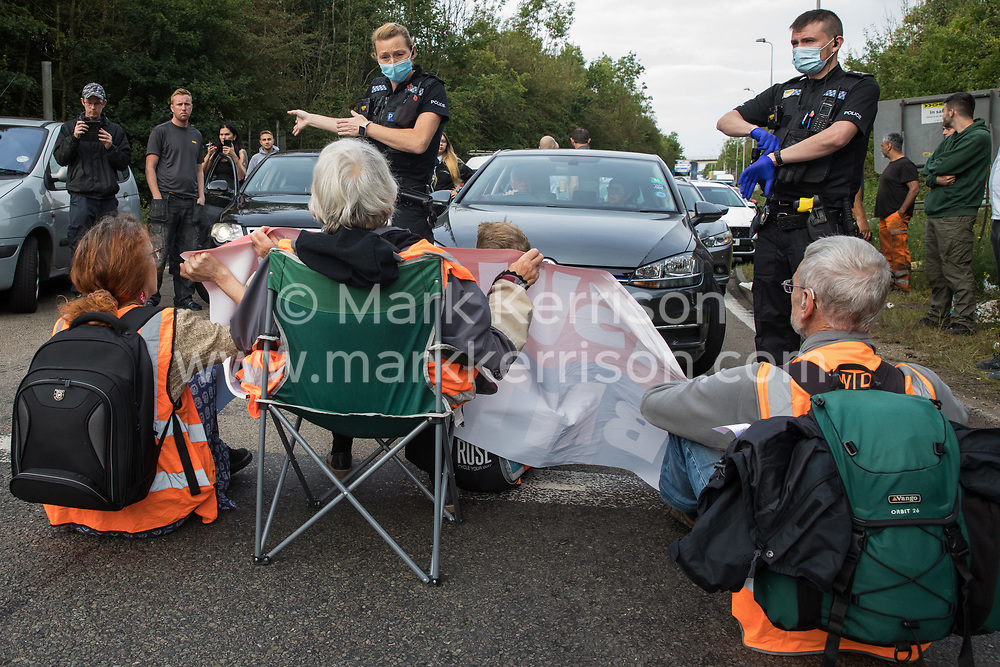 A police officer asks Insulate Britain climate activists to move out of a slip road from the M25 which they had blocked, causing a long tailback on the motorway, as part of a new campaign intended to push the UK government to make significant legislative change to start lowering emissions on 13th September 2021 in Godstone, United Kingdom. The activists, who wrote to Prime Minister Boris Johnson on 13th August, are demanding that the government immediately promises both to fully fund and ensure the insulation of all social housing in Britain by 2025 and to produce within four months a legally binding national plan to fully fund and ensure the full low-energy and low-carbon whole-house retrofit, with no externalised costs, of all homes in Britain by 2030 as part of a just transition to full decarbonisation of all parts of society and the economy.