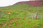 Israel, Golan Heights, an old pre Six Day War minefield with fence and warning signs. On February 6 2010 two Israeli children were seriously injured when they walked into a snow covered minefield. A gap in the fence is the main danger of these old fields