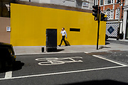 A businessman holds a conversation into his phone alongside a yellow construction hoarding in Mayfair, on 16th July 2021, in London, England.