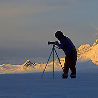 """A ski mountaineer takes pictures from the Calley Glacier on the Antarctic Peninsula, Antarctica.  Behind is a summit sometimes called """"Wiltsie's Peak."""""""