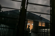 """A woman who was pregnant by a rape stands at the doorstep in a transit center, where other victims who survived from sexual violence, at Keshero Hospital in Goma, North Kivu. <br /> """"It has probably become more dangerous to be a woman than a soldier in an armed conflict,"""" said Patrick Cammaert, a former UN force commander. Due to a decade-long armed conflict in the Eastern Congo, it has been the Congolese women who have been suffering from the worst kind of the sexual violence in the world: using rape as a weapon of war. In the peak year of 2007, the sexual violence recorded 13,247 cases a year; approximately 36 rape cases a day. Although the number of the """"cases"""" has been dwindled to 4,689 cases a year in 2011, the number has again increased since 2012 when the new rebellion called M23 mutinied against the Congolese Army (FARDC) and the government until the end of 2013. However, the sufferings of women did not end with the peace accords. The victims, who barely survived from the rapes – often by deadly gang rapes with additional assaults – continue to be afflicted by the physical, psychological, and socio-economic trauma long after the end of the conflict."""