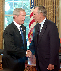 Washington, D.C. - September 1, 2005 -- United States President George W. Bush shakes hands with his Dad, former United States President George H.W. Bush, after he named him and former United States President George H.W. Bush as co-chairs of an effort to raise money to help those affected by Hurricane Katrina. Photo by Ron Sachs/ CNP/ABACAPRESS.COM