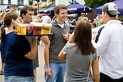 Waitress delivering beer and other drinks to people having fun. Grand Old Day Street Fair St Paul Minnesota USA