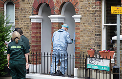 © Licensed to London News Pictures. 15/08/2018. London, UK. An investigator in a protective suit enters a house where a woman has been stabbed to death in Battersea, South London as ambulance workers stand by (L). A 40 year old male was arrested at the scene on suspicion of murder. Photo credit: Peter Macdiarmid/LNP