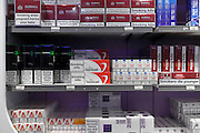 various brands of cigarettes with big lettered warning text at a airport duty free shop
