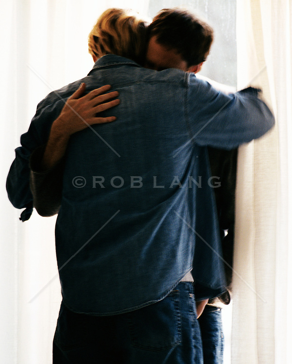 two men holding each other in front of a window