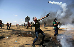 May 11, 2018 - Khan Younis, Gaza Strip, Palestinian Territory - A Palestinian protester uses a racket to throw back a tear gas canister fired by Israeli security forces during clashes in tents protest where Palestinians demanding the right to return to their homeland, at the Israel-Gaza border, in Khan Younis in the southern Gaza Strip.  (Credit Image: © Ashraf Amra/APA Images via ZUMA Wire)