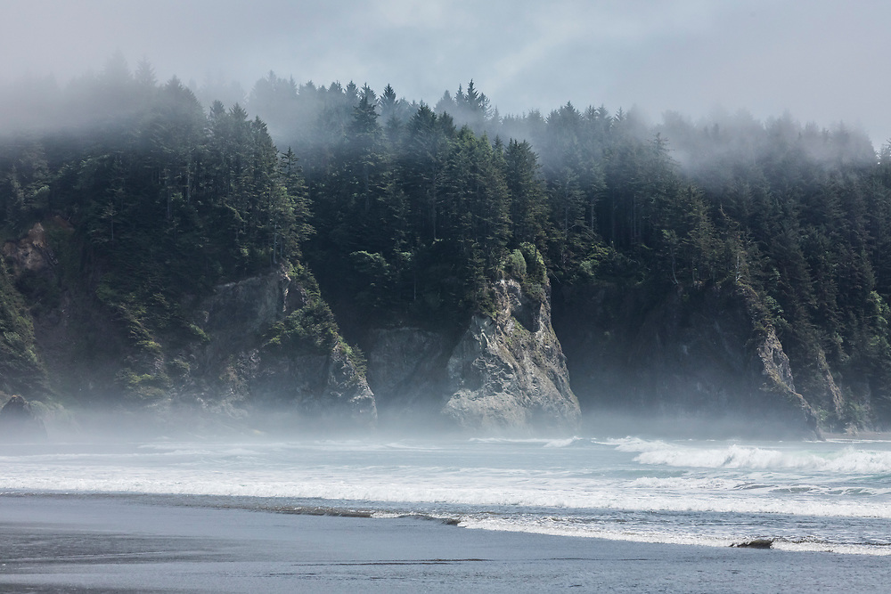 Salt spray hanging above the surf and low clouds drifting into the forests above the rock cliffs, 2nd Beach, Olympic National Park Coastal Preserve, Washington USA.