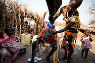 A young boy recives a hair cut upon his return to his family after two years kidnapped by the Murle tribe.