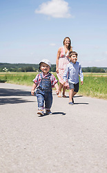 Woman with his son walking on road in the countryside, Bavaria, Germany