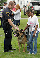 Middletown, New York - Two girls and a police officer pet his police dog Kilo at the festival following the 15th annual Ruthie Dino Marshall 5K Run and Fun Walk hosted by the Middletown YMCA on Sunday, June 5, 2011.