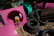 Boy climbs through tunnels in risk averse playground called The Land on Plas Madoc Estate, Ruabon, Wrexham, Wales. A young kid explores the tunnels and tyres in a way that parents are nowadays scared to allow. But here in this council play park, children are encouraged to experiment with risk aversion, to enjoy a wilder form of play and interaction with others - the opposite of online relations and over safe childhoods. From the chapter entitled 'Playing with Fire' from the book 'Risk Wise: Nine Everyday Adventures' by Polly Morland (Allianz, The School of Life, Profile Books, 2015).
