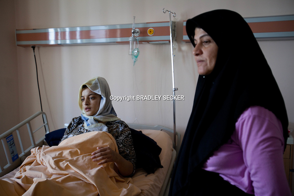 A young Syrian girl lays in hospital in Antakya, Turkey, with her mother. Whilst fleeing towards the Syrian border her group of refugees reportedly camp under attack by the Syrian military near Lattakia, Syria. 12/06/2012