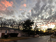 Merrick, New York, USA. January 24, 2019. After flash flood, reflection of colorful winter sunset fills large puddle in road of suburban town on south shore of Long Island.