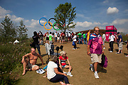 London, UK. Thursday 9th August 2012. London 2012 Olympic Games Park in Stratford. People up on the hill near to the Olympic rings relaxing in the sunshine.