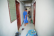 Oct. 6, 2009 -- SAMUT SAKHON, THAILAND: TUN, a Burmese migrant in Samut Sakhon walks through the hallway of his tenement in Samut Sakhon, Thailand. The Thai fishing industry is heavily reliant on Burmese and Cambodian migrants. Burmese migrants crew many of the fishing boats that sail out of Samut Sakhon and staff many of the fish processing plants in Samut Sakhon, about 45 miles south of Bangkok. Migrants pay as much $700 (US) each to be smuggled from the Burmese border to Samut Sakhon for jobs that pay less than $5.00 (US) per day.   Photo by Jack Kurtz / ZUMA Press