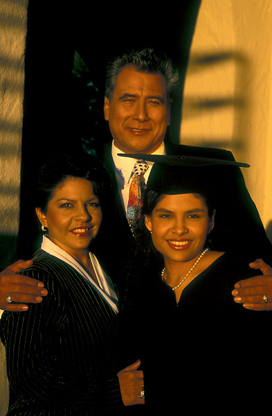 Stock photo of Hispanic parents with their daughter at her graduation