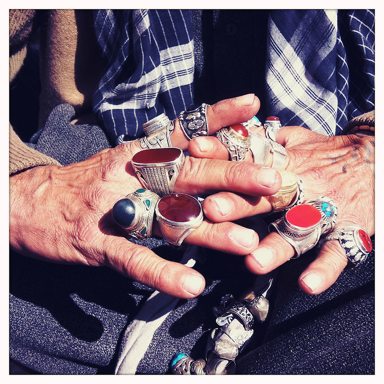 A man displays rings for sale.