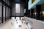 People come and go in the Turbine Hall at Tate Modern museum for Modern Art on the Southbank of London. This has become a cathedral for Contemporary arts.