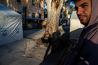 LEROS, GREECE - FEBRUARY 07: Iraqi-Kurdish refugees, 26 years-old Ahmad (right) and 30 years-old Shakavanh (left) stand on a square inside Leros refugee camp on February 07, 2015 in Leros, Greece. Hundreds of refugees are assisted by volunteers and Ngo's staff at the Leros refugee camp while waiting to board a ferry to travel to Athens. Photo: © Omar Havana. All Rights Are Reserved