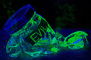 """A glowing mason jar labeled """"Evil"""" lies broken on a cement floor as green smoke escapes from its  glass fragments.Black light"""