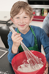 Boy whipping cream with wire whisk in home economics class, Bavaria, Germany