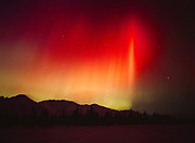 Brilliant red and green aurora casting purplish color on snow of the Talkeetna Mountains and Colorado Lake, geomagnetic storm during early morning hours, March 31, 2001, Broad Pass, Alaska.