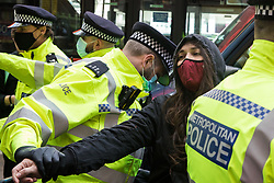London, UK. 11th May, 2021. A Metropolitan Police officer searches an activist during a protest by Palestine Action outside the UK headquarters of Elbit Systems, an Israel-based company developing technologies used for military applications including drones, precision guidance, surveillance and intruder-detection systems. The activists were protesting against the company's presence in the UK and in solidarity with the Palestinian people following attempts at forced evictions of Palestinian families in the Sheikh Jarrah neighbourhood of East Jerusalem, the deployment of Israeli forces against worshippers at the Al-Aqsa mosque during Ramadan and air strikes on Gaza which have killed several children.