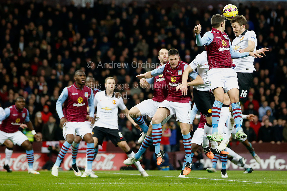 Michael Carrick of Manchester United (r) rises highest to meet a corner kick. Barclays Premier league match, Aston Villa v Manchester Utd at Villa Park in Birmingham on Saturday 20th December 2014<br /> pic by Mark Hawkins, Andrew Orchard sports photography.