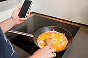 Household chores. Woman cooks while using her smartphone to communicate and work